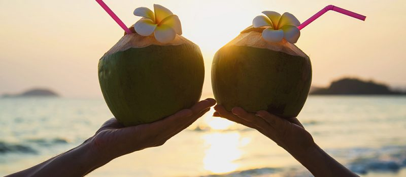 fresh coconut in couples hands with plumeria decorated on beach with sea wave background - tourist with fresh fruit and sea sand sun